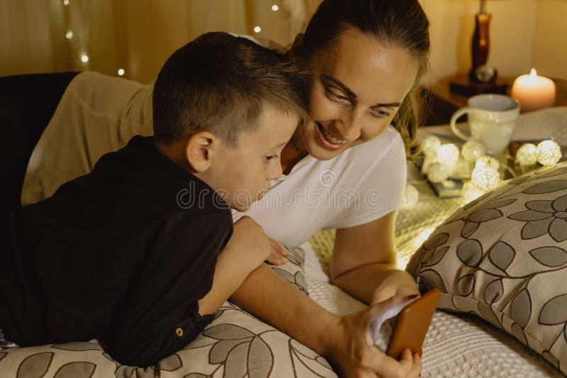 Enfantez et son fils regardant des bandes dessinées au téléphone dans le lit avant d'aller photographie stock