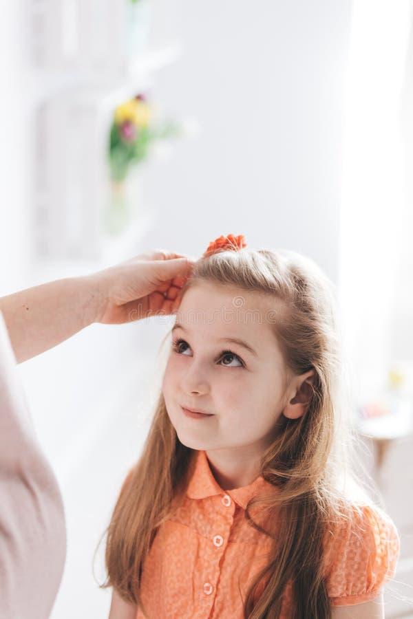 Enfantez fixer ses jeunes cheveux du ` s de fille image libre de droits