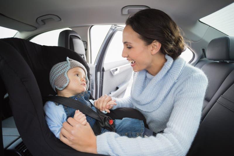 Enfantez fixer son bébé dans le siège de voiture photo stock