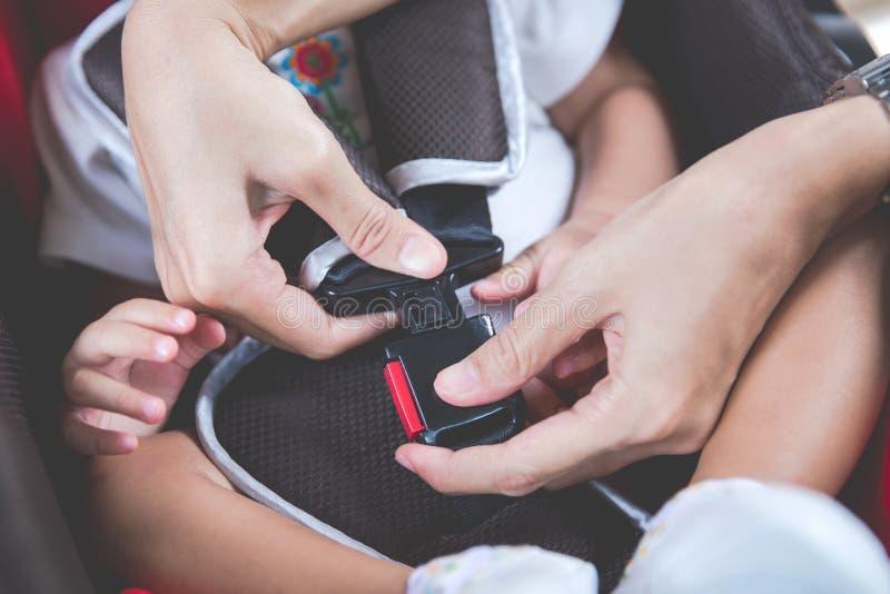 Enfantez fixer son bébé dans le siège de voiture dans sa voiture image stock