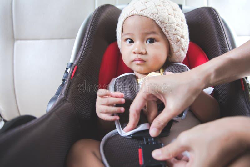 Enfantez fixer son bébé dans le siège de voiture dans sa voiture photos stock