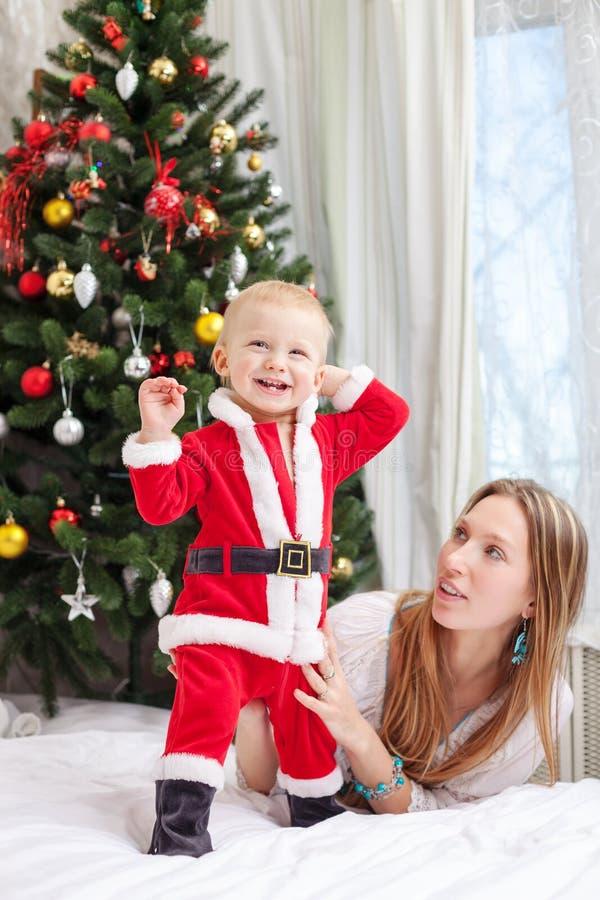 Enfantez jouer avec le bébé habillé dans le costume de Santa photos stock