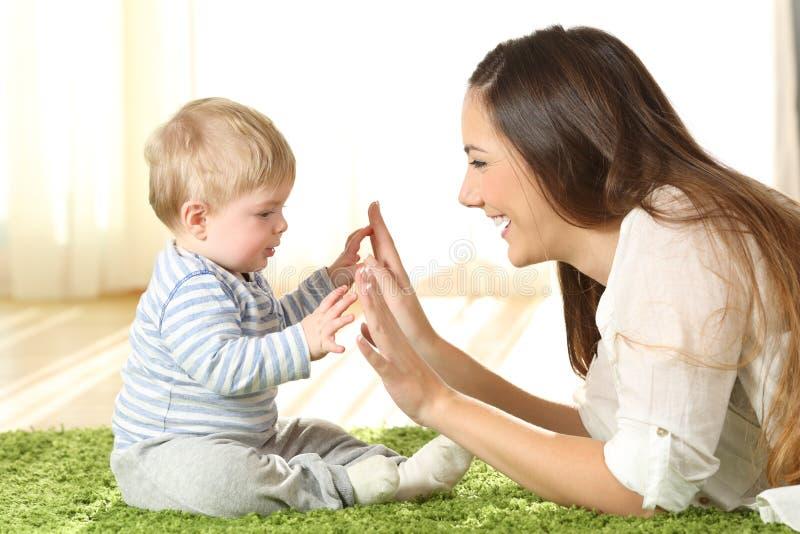 Enfantez jouer avec son bébé sur un tapis photo stock