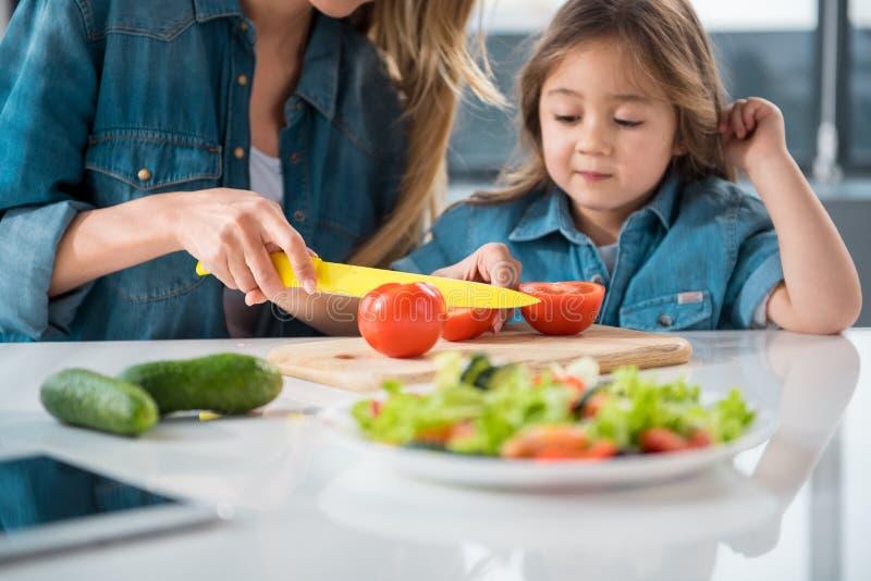 Enfantez la fille de enseignement comment faire une salade image stock