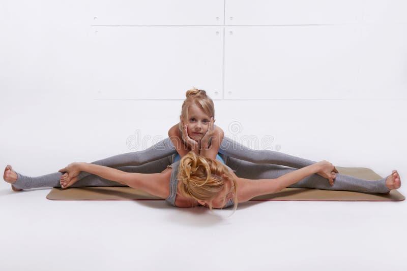 Enfantez la fille faisant l'exercice de yoga, sports de famille de forme physique, femme appareillée par sports s'asseyant sur le photographie stock libre de droits
