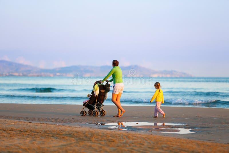 Enfantez la marche sur la plage avec sa fille et bébé photographie stock
