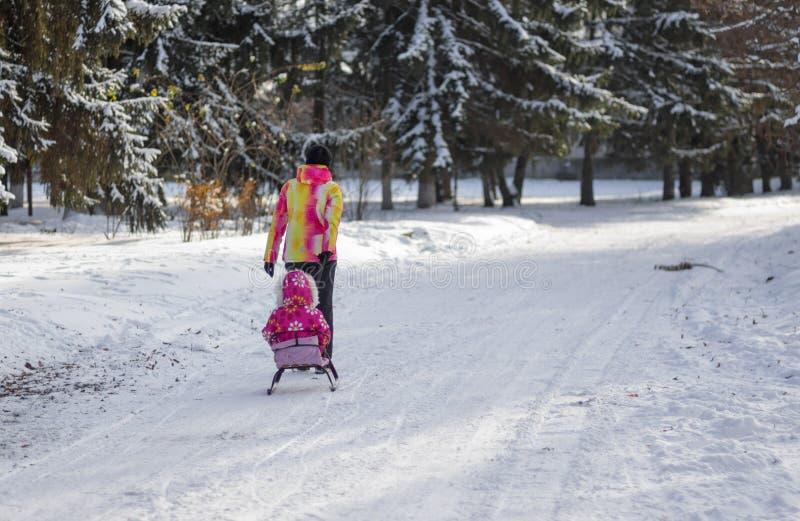 Enfantez la marche sur une rue vide et neigeuse conduisant le traîneau avec l'enfant dans Dniepr, Ukraine chez décembre, 04 2016 images stock