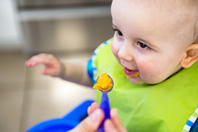 Enfantez le bébé affamé de alimentation dans le highchair à l'intérieur photos libres de droits