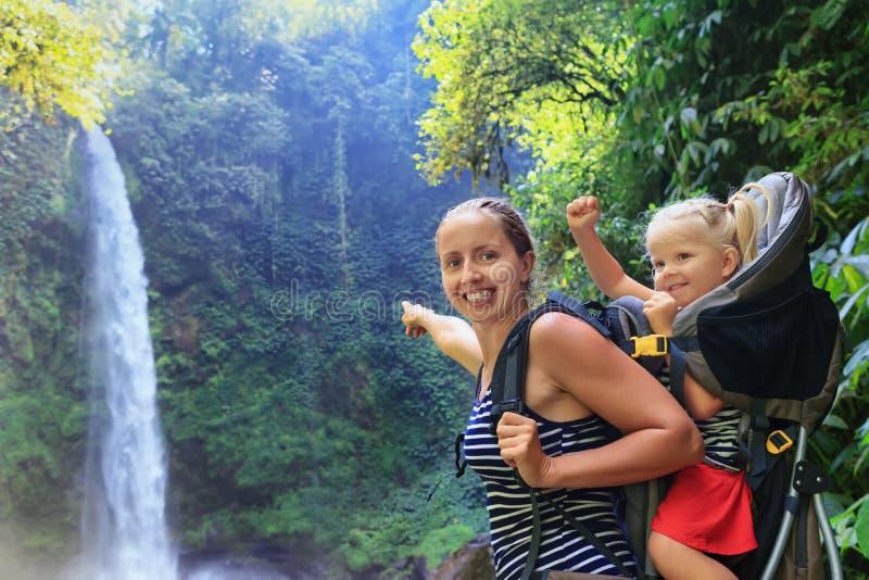 Enfantez le bébé de prise dans le sac à dos sur le fond de cascade images libres de droits
