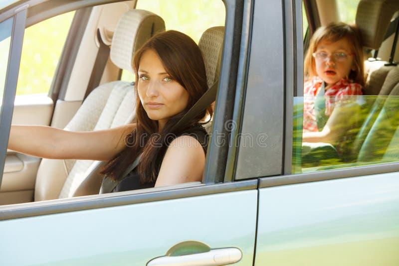 Enfantez le conducteur et la petite fille dans le siège de sécurité de voiture photos stock