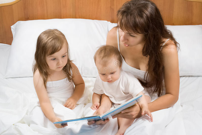 Enfantez le livre d'histoire de temps de lit de lecture aux enfants photographie stock libre de droits
