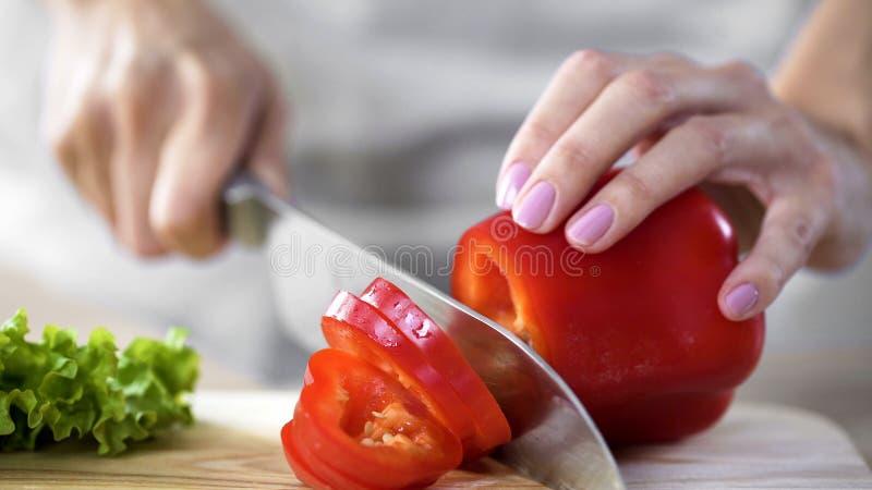 Enfantez le poivre de coupe pour la salade de déjeuner dans la cuisine à la maison, des soins de santé, passe-temps photos libres de droits