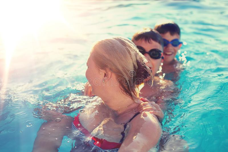 Enfantez le regard de nouveau aux fils de sourire dans la piscine photos stock