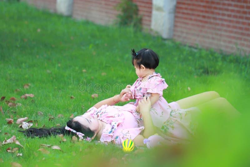 Enfantez les jeux de jeu avec son petit bébé sur la pelouse images stock