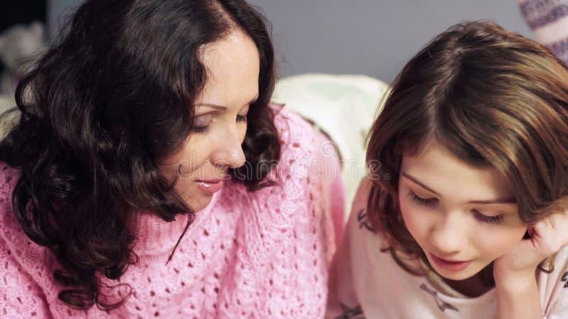 Enfantez parler avec la fille avant heure du coucher, moments doux ensemble, plan rapproché image libre de droits