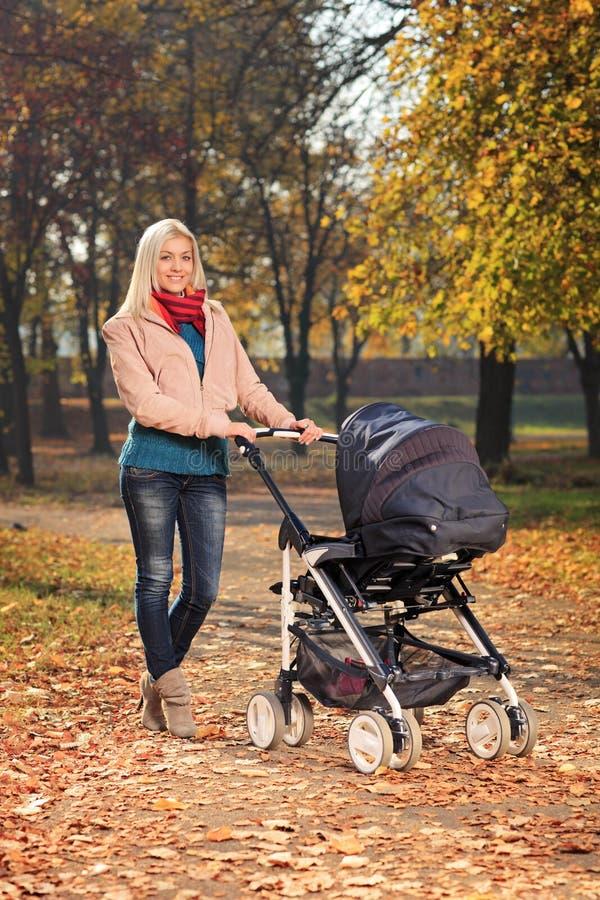 Enfantez pousser une poussette de chéri en stationnement en automne image libre de droits