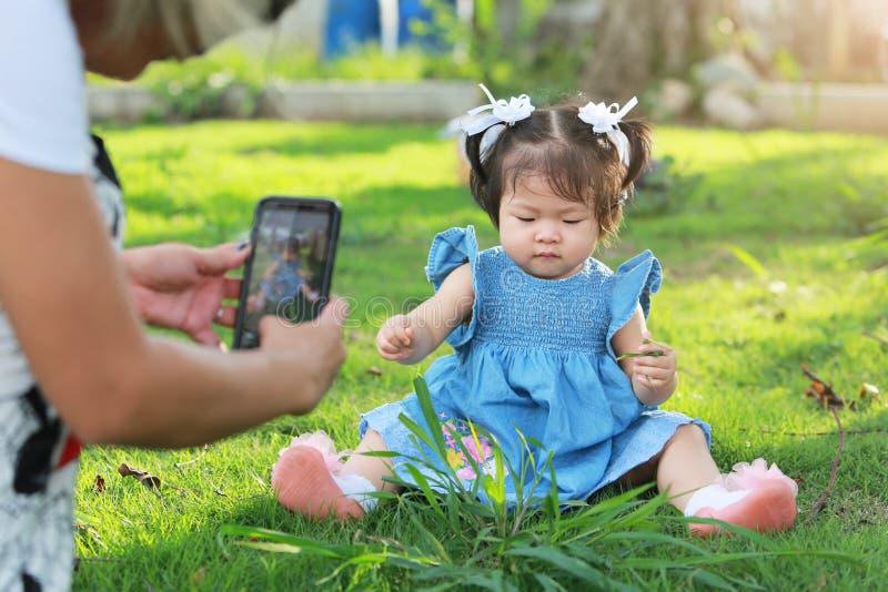 Enfantez prendre une photo avec sa fille de bébé s'asseyant sur la cour image libre de droits