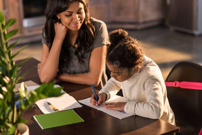 Enfantez regarder la petite fille mignonne faisant des devoirs, concept d'aide de devoirs image stock