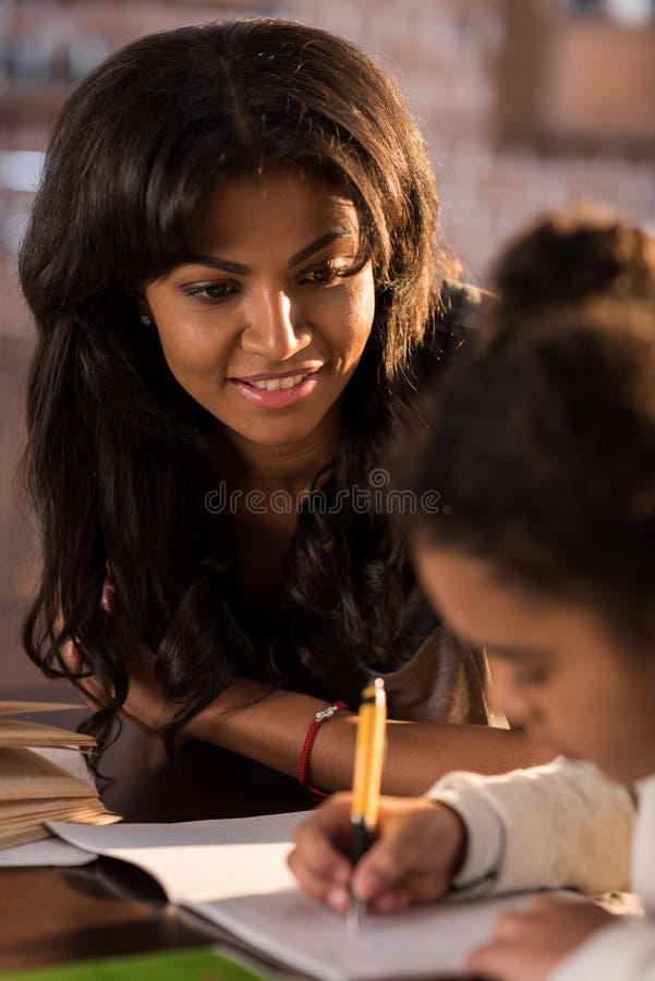Enfantez regarder la petite fille mignonne faisant le travail à la maison photos stock