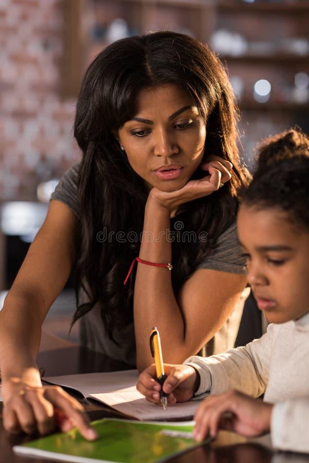 Enfantez regarder la petite fille mignonne faisant le travail à la maison photographie stock libre de droits