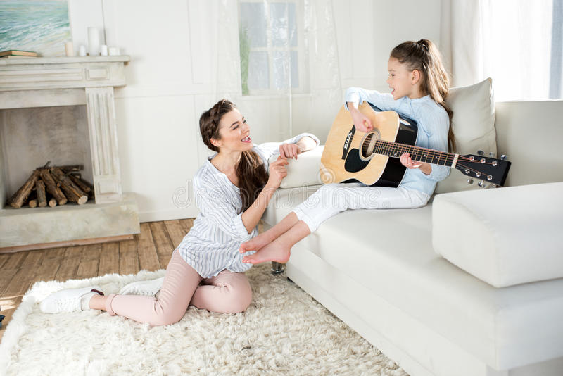 Enfantez se reposer sur le tapis et regarder la fille de sourire jouant la guitare image stock
