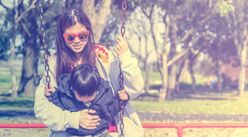 Enfantez tenir son enfant sur un terrain de jeu d'oscillation avec l'espace de copie photos libres de droits