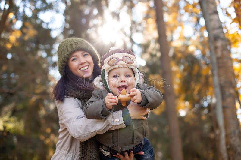 Enfantez tenir son petit fils dans le chapeau pilote et jouer dans l'avion de jouet photographie stock libre de droits