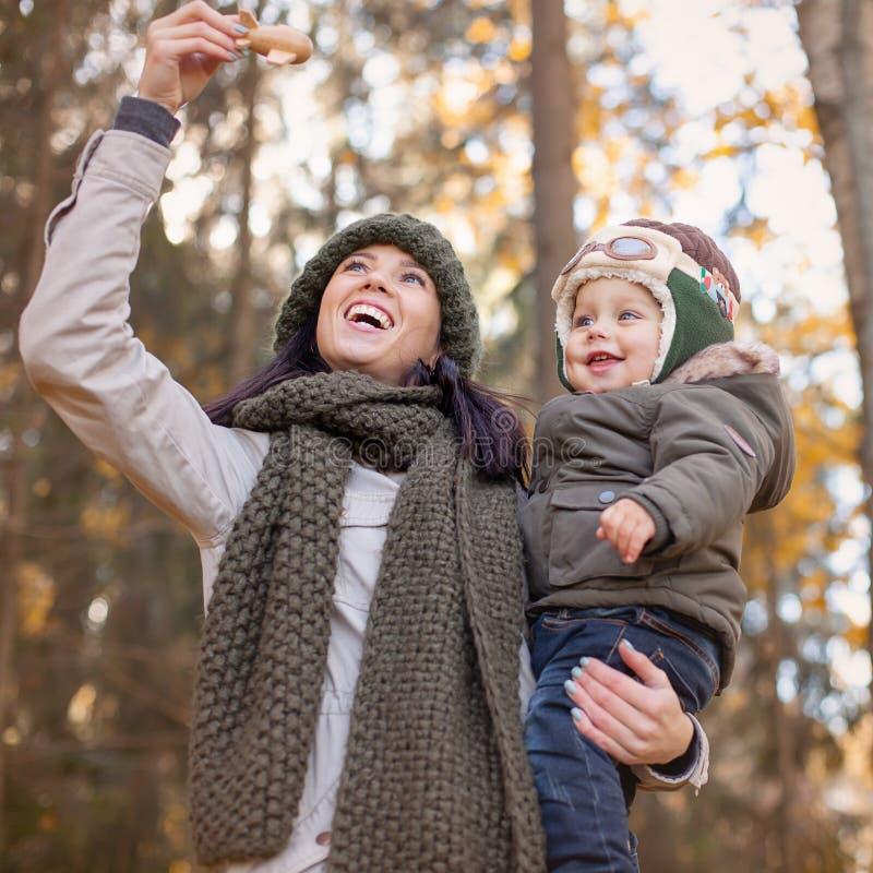 Enfantez tenir son petit fils dans le chapeau pilote et jouer dans l'avion de jouet photos libres de droits