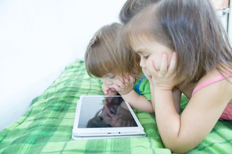 Enfants à l'aide du comprimé se trouvant sur le lit à la maison Dépense de temps d'enfants Enfants à l'aide du comprimé image stock