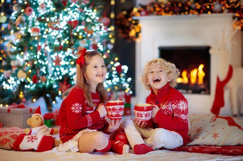 Enfants à l'arbre de Noël Les enfants boivent du cacao chaud photographie stock