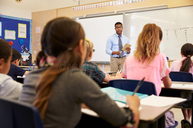 Enfants écoutant le professeur à une classe d'école primaire image libre de droits