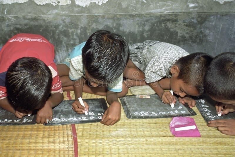 Enfants écrivant avec la craie sur des ardoises, Bangladesh photographie stock libre de droits