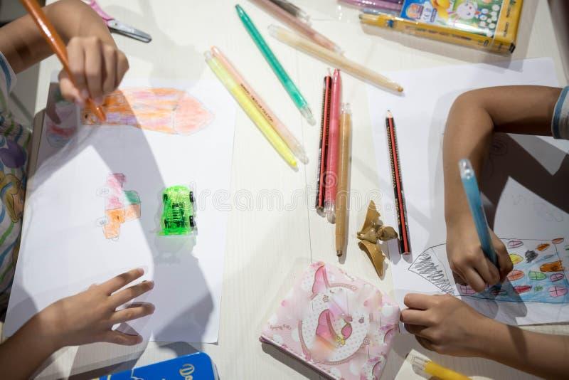 Enfants écrivant la coloration de dessin sur le papier utilisant le crayon photographie stock