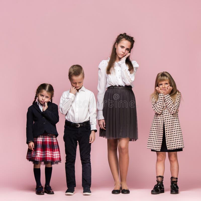 Enfants élégants mignons sur le fond rose de studio Les beaux filles et garçon de l'adolescence se tenant ensemble photos libres de droits