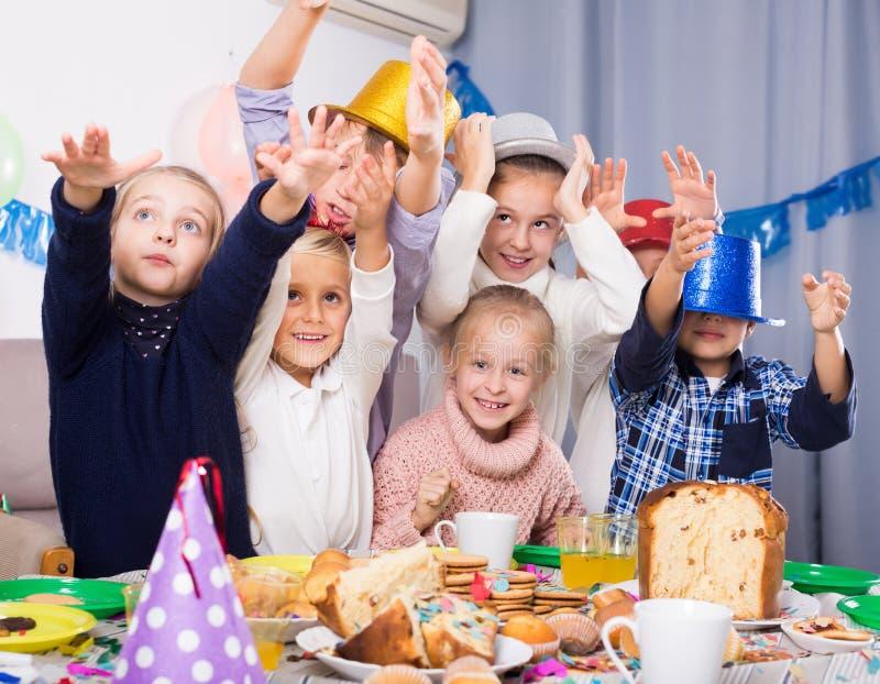 Enfants actifs de groupe ayant la fête d'anniversaire d'amusement image libre de droits