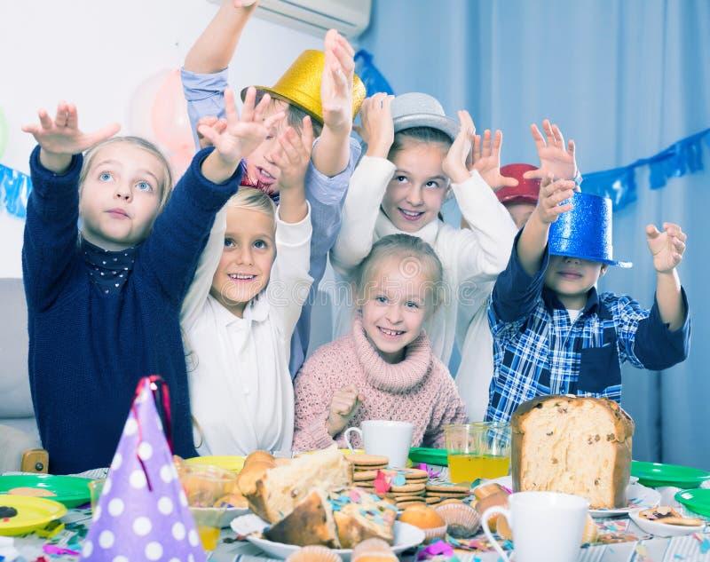 Enfants actifs de groupe ayant la fête d'anniversaire d'amusement photo libre de droits