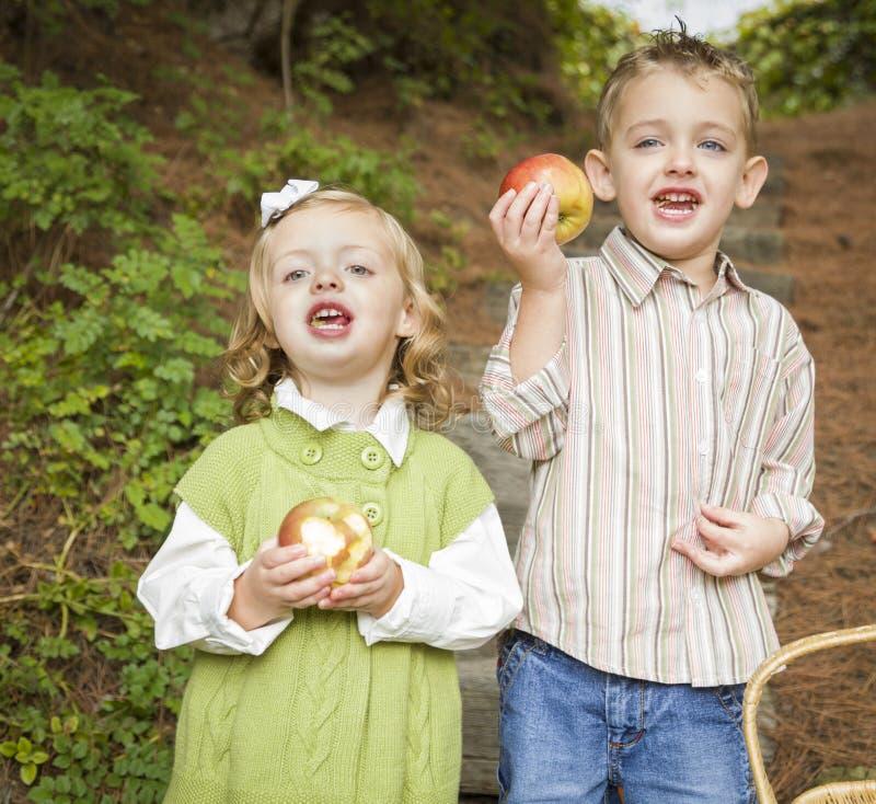 Enfants adorables mangeant les pommes rouges dehors photo libre de droits
