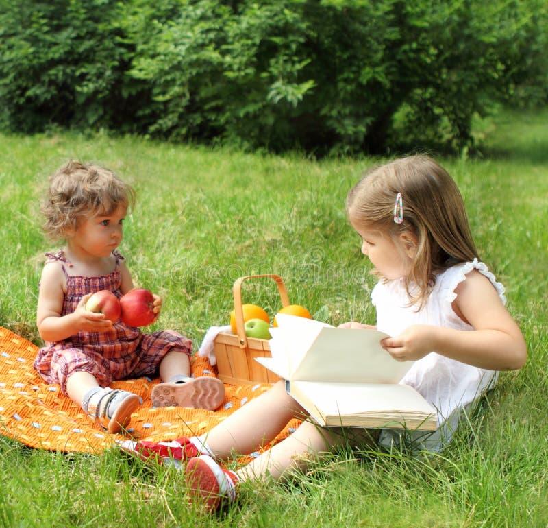 Enfants affichant le livre sur le pique-nique photo stock