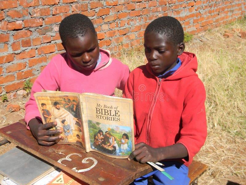 Enfants africains lisant un livre d'histoires de bible image stock