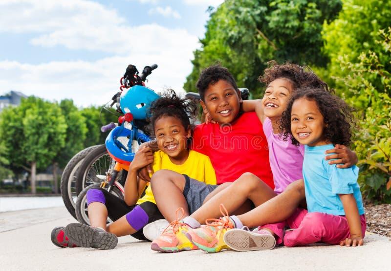 Enfants africains s'asseyant sur la ruelle de cycle en été photo stock
