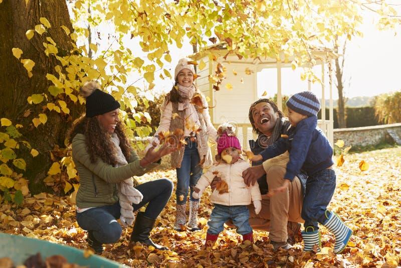 Enfants aidant des parents à rassembler Autumn Leaves In Garden photos libres de droits