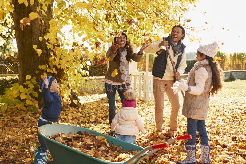 Enfants aidant des parents à rassembler Autumn Leaves In Garden photographie stock libre de droits