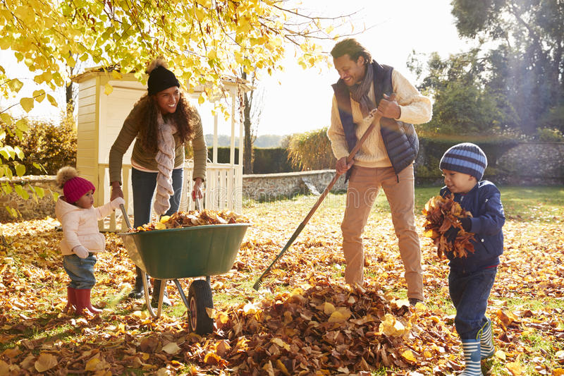 Enfants aidant des parents à rassembler Autumn Leaves In Garden image libre de droits