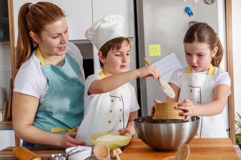 Enfants aidant la mère dans la cuisine faisant cuire au four ensemble image stock