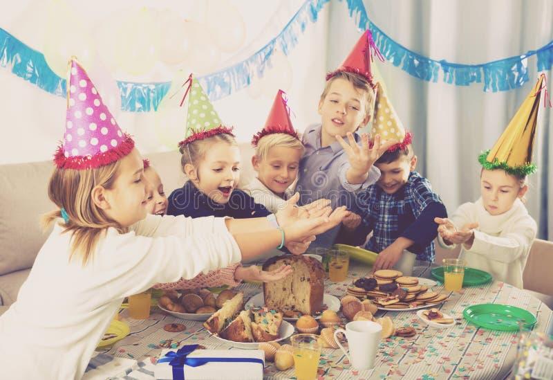 Enfants amicaux appréciant le dîner de fête de friend's photos stock