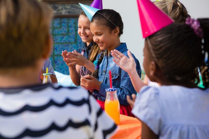 Enfants applaudissant tout en se reposant à la table photos libres de droits
