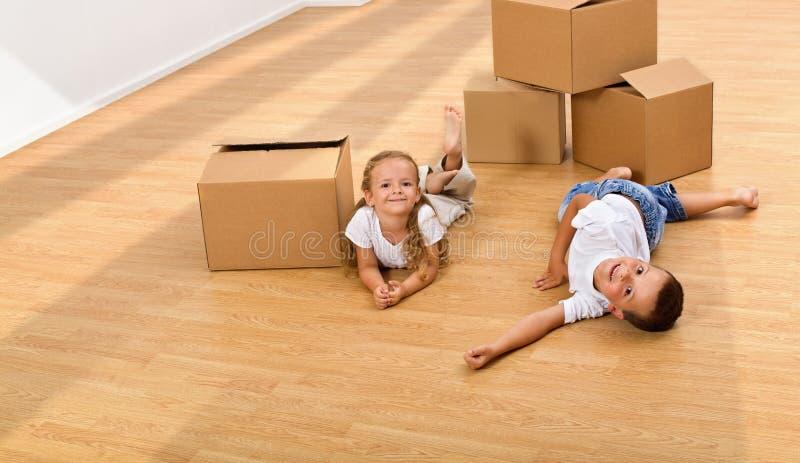 Enfants appréciant le grand espace dans leur nouvelle maison photo stock