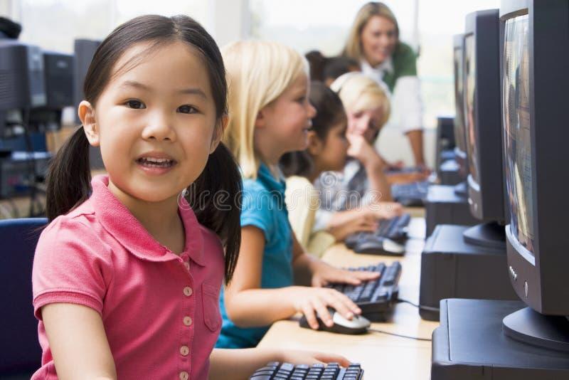 Enfants apprenant comment utiliser des ordinateurs. images stock