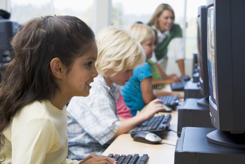 Enfants apprenant comment utiliser l'ordinateur image libre de droits