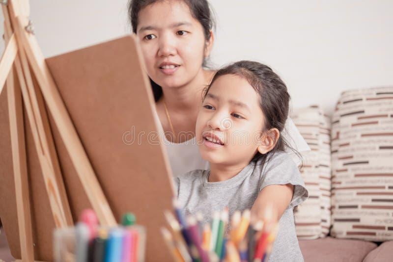 Enfants apprenant la peinture avec le parent images stock